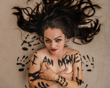 """I am mine"" with designer Amanda Casarez"" Photos by Marcus Carter. Amanda is topless and covered in black hand prints, with red lipstick. Style concept by editorial stylist Patty Chism"