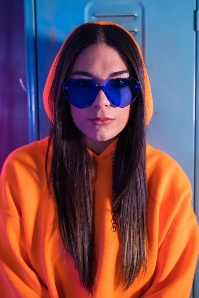 Caroline Torti styled in Untitled and Co. orange crop hoodie and blue heart shaped sun glasses.