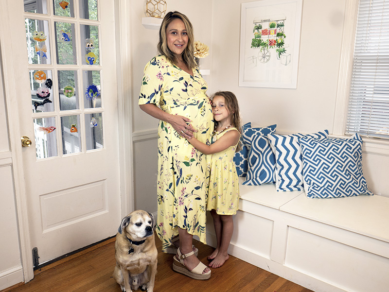 Patty Chism in yellow wrap dress standing with daughter and dog.